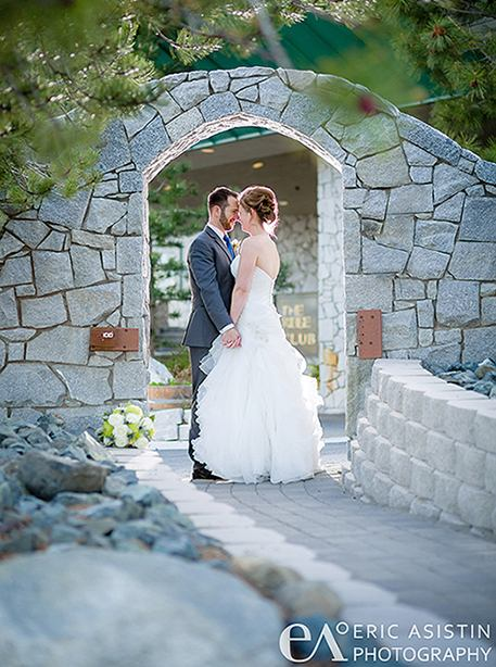 bride and groom under a stone arch
