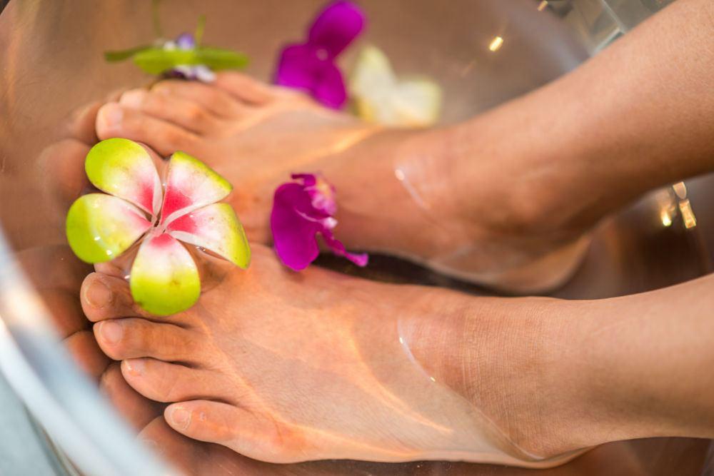 woman's feet in flower infused water