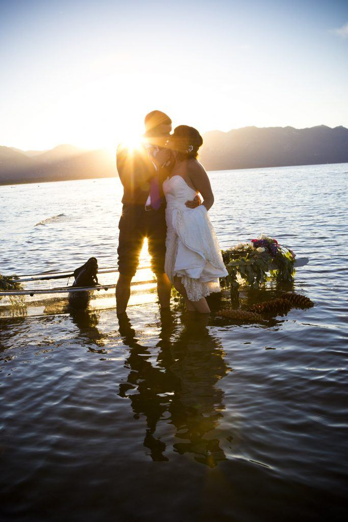 Newlywed couple looking at a sunset on lake tahoe