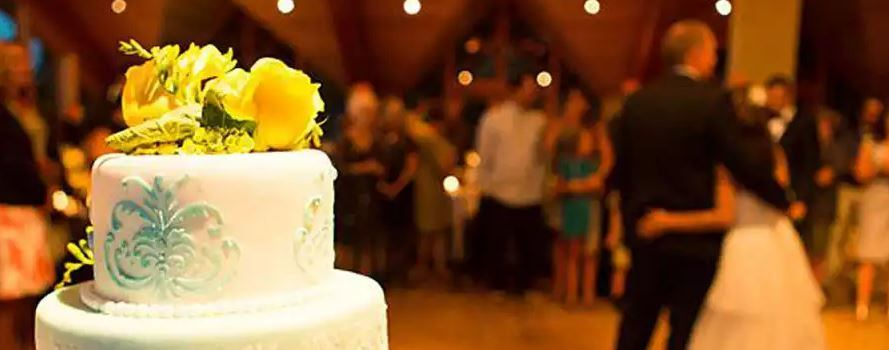 wedding cake in the foreground of a wedding scene