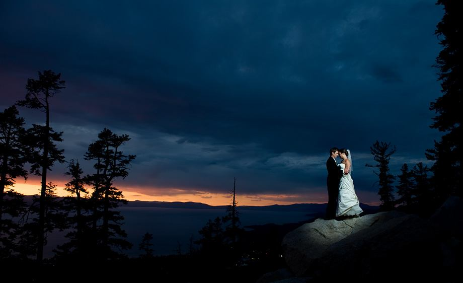 newlyweds posing in front of an evening sky