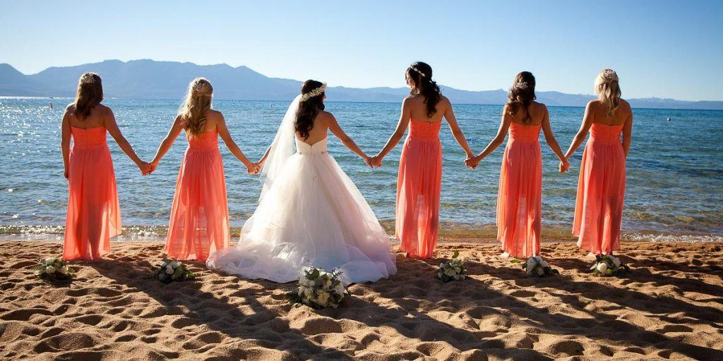 bride and bridesmaids holding hands on the beach