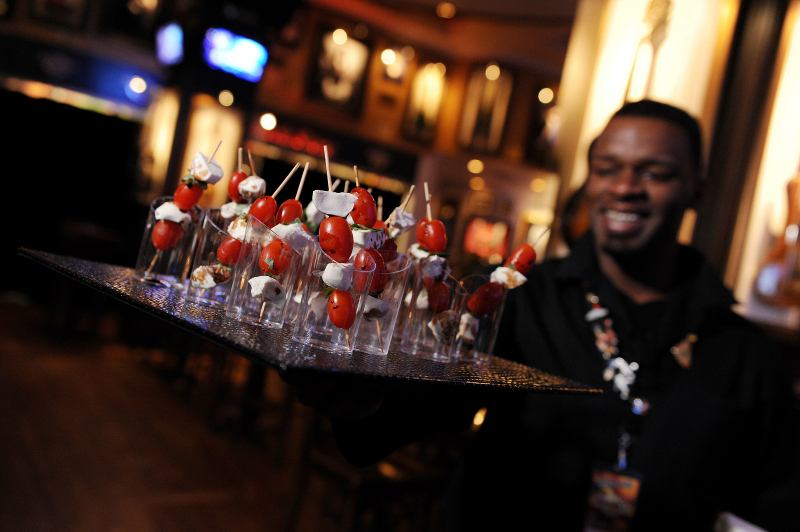 african american server carrying a tray of drinks