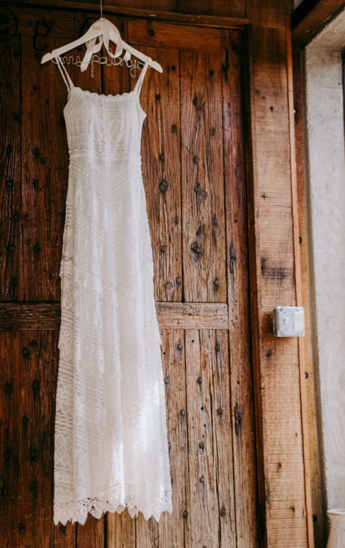 lace wedding dress hanging on a pine wall