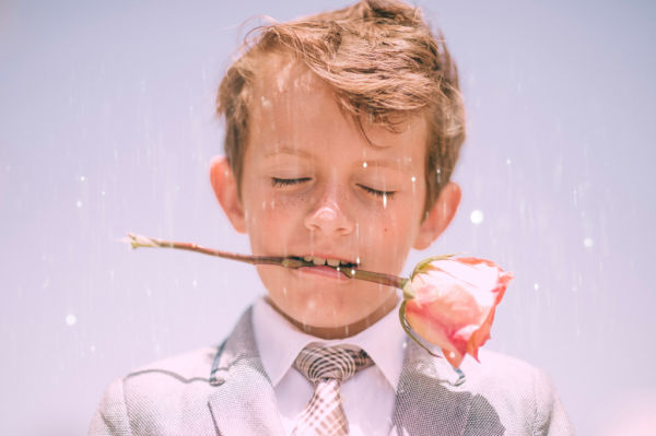boy ring bearer holding flower in his mouth