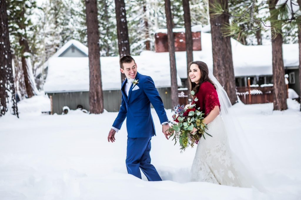 bride and groom walking hand in hand in the snow