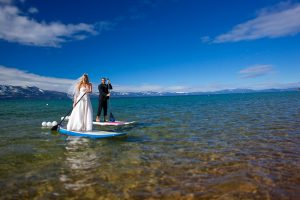 bride and groom stand up paddle boarding