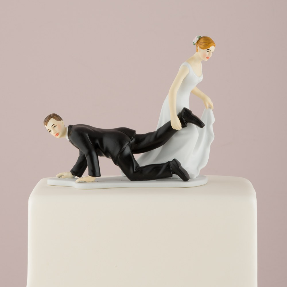 comical wedding cake topper with bride dragging groom