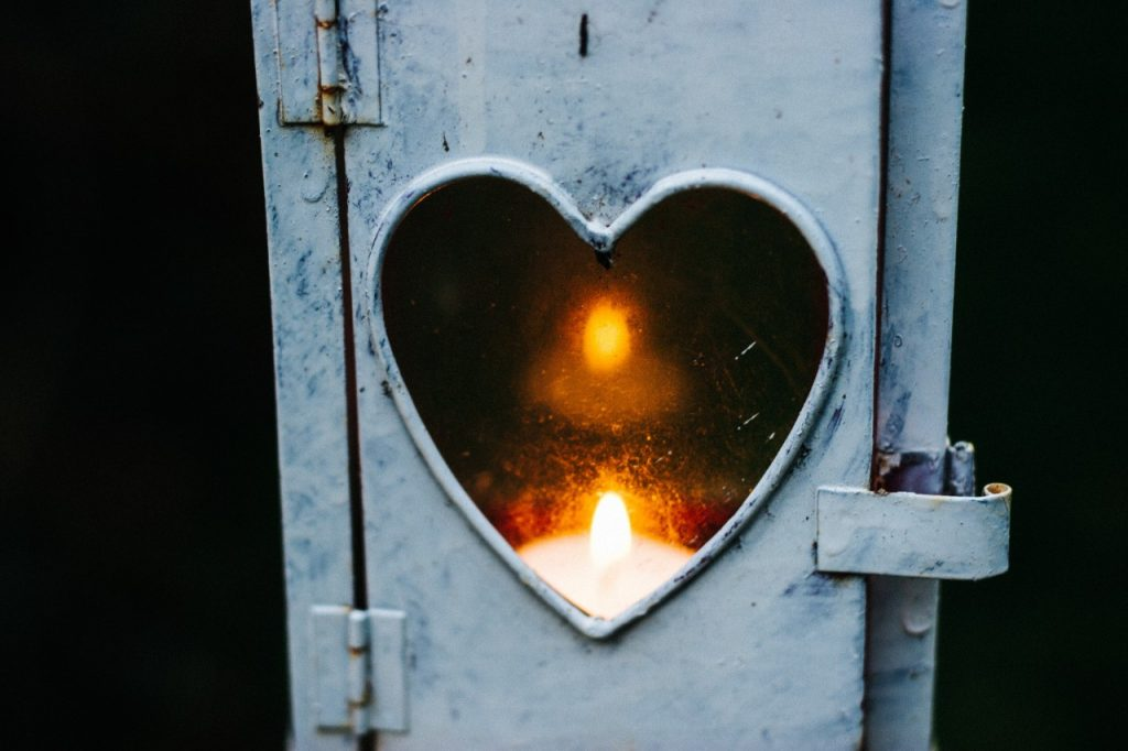 lit candle inside a heart shaped box